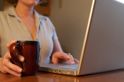 Woman enjoys her morning coffee in the kitchen while checking her email or paying the bills.